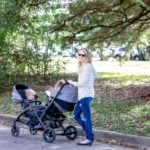Mom with two kids in the stroller at the park
