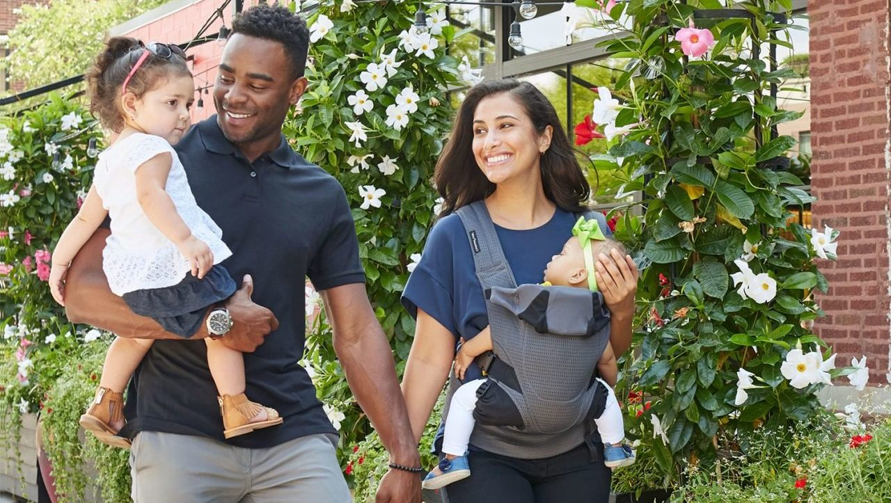 Parents walking with Child and Baby in Contours Carrier