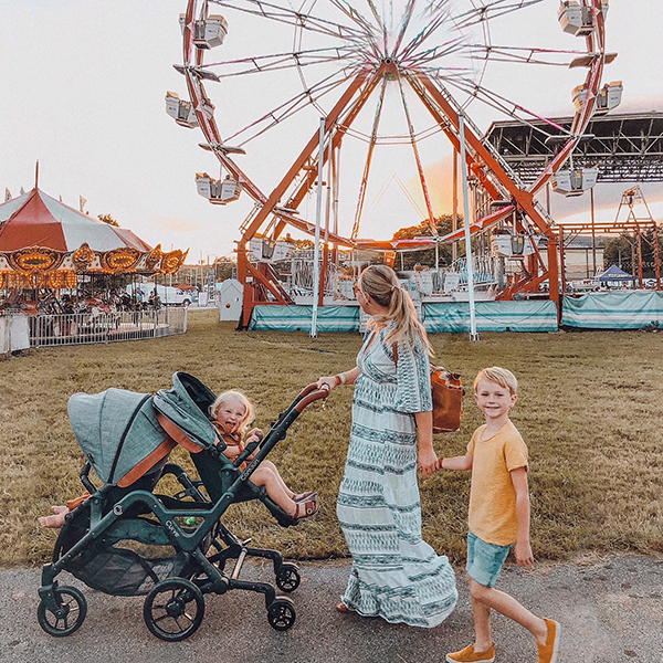 Mom strolling with kids in the Curve stroller