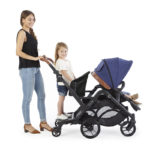 Mom with toddler standing using the Curve Sit & Boogie Jump Seat & Platform accessory