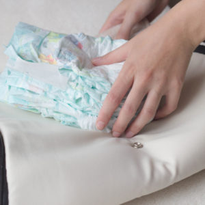 hands packing diaper bag