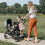 Mom with kid standing using the Options Sit & Boogie Jump Seat and Platform accessory
