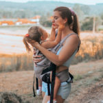 Mom carrying child in the Journey GO carrier carrier