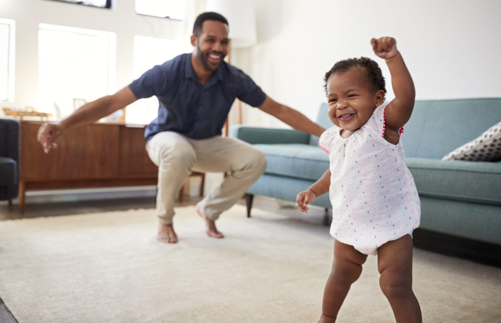 Baby dancing with dad at home