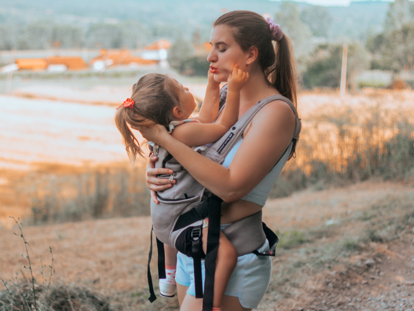 Mom carrying baby in the facing-in position in the Journey GO Carrier